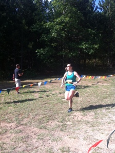 Marla sprinting toward the finish of her first trail half marathon